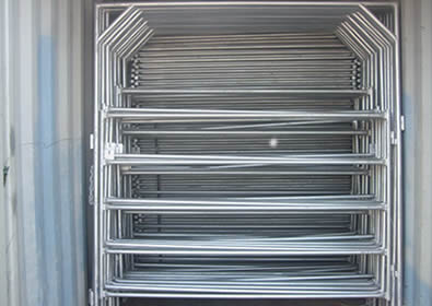 Many galvanized round pipe gates in bulk in container
