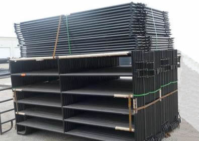 Many black powder coated fence panels packed
